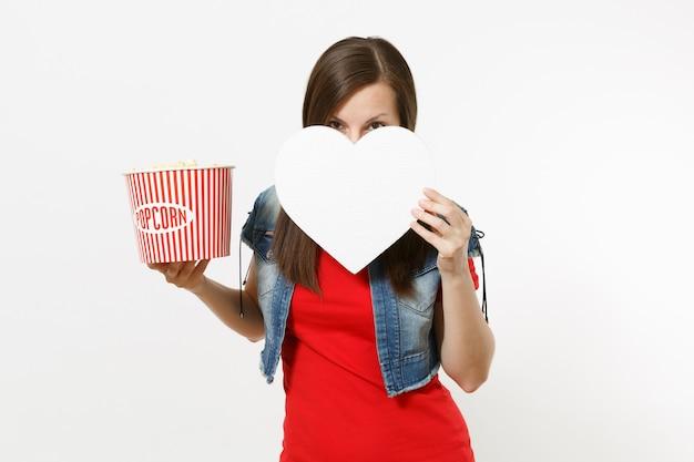 캐주얼 옷을 입고 영화를 보고, 팝콘 양동이를 들고 흰색 배경에 격리된 복사 공간이 있는 하얀 마음으로 얼굴을 덮고 있는 젊은 브루네트 여성의 초상화. 영화 속 감정.