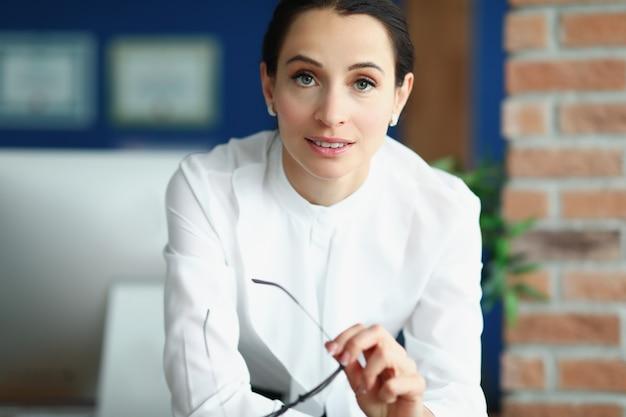Портрет молодой женщины брюнетки в офисе