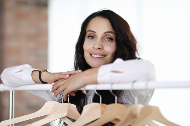 Портрет молодой женщины брюнетки возле стойки с вешалками