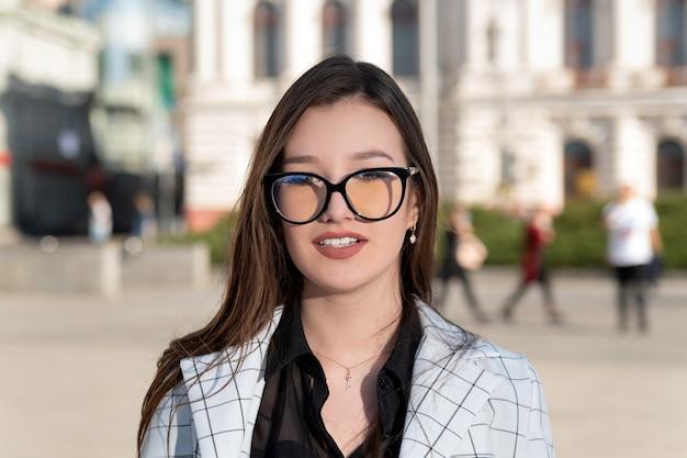Портрет молодой женщины брюнет в очках. студент на фоне института. учитель аспирантуры.