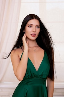 Портрет молодой женщины брюнетки с длинными здоровыми волосами