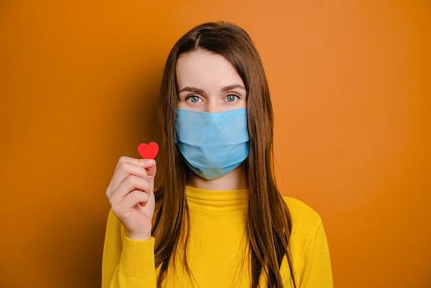 小さな赤いハートを保持している茶色の背景に分離された保護の青いフェイスマスクを持つ若いブルネットの女性の肖像画。家にいる検疫コロナウイルスのパンデミック予防。自宅検疫