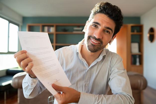 家にいる間、仕事のビデオ通話で紙に何かを示している若いビジネスマンの肖像画。ホームオフィス。