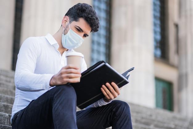 屋外の階段に座ってフェイスマスクを着用し、ファイルを読んでいる若いビジネスマンの肖像画。ビジネスコンセプト。新しい通常のライフスタイルのコンセプト。