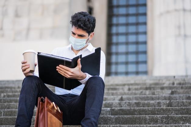 屋外の階段に座ってフェイスマスクを着用し、ファイルを読んでいる若いビジネスマンの肖像画。