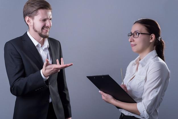 Портрет молодых деловых людей в деловой одежде. парень возмущен отчетом деловой девушки с папкой для документов.