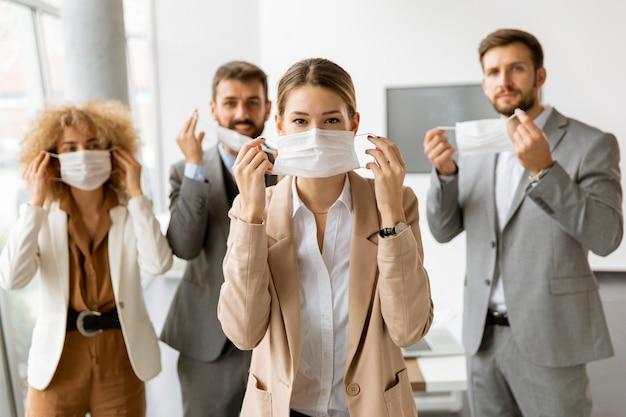 オフィスで彼らの保護フェイスマスクを脱いで若いビジネスマンの肖像画