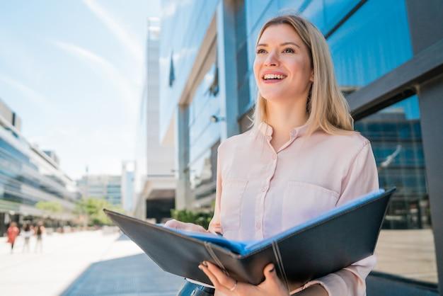 通りで屋外に立っている間クリップボードを保持している若いビジネス女性の肖像画。ビジネスコンセプトです。