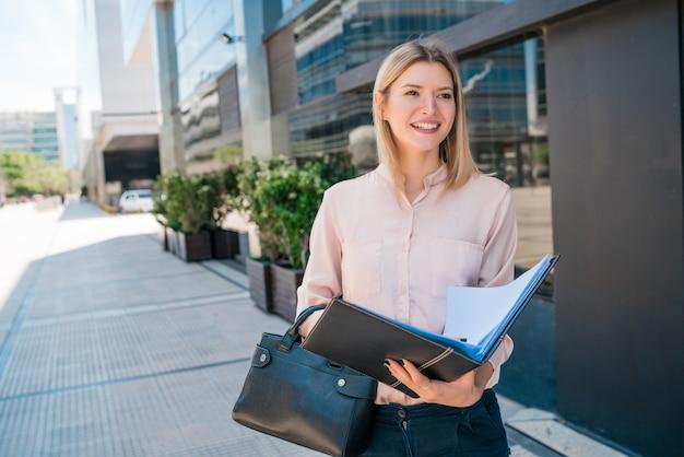 通りで屋外に立っている間クリップボードを保持している若いビジネス女性の肖像画。ビジネスコンセプト。