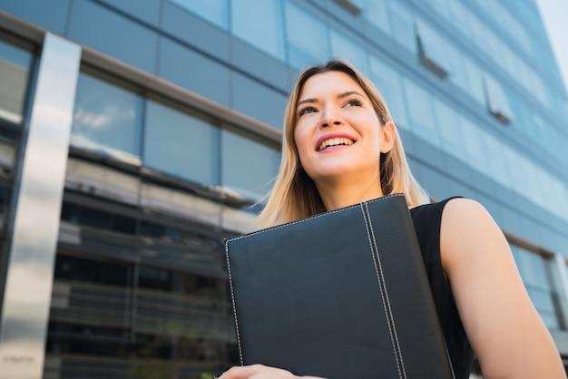 Портрет молодой деловой женщины, держащей буфер обмена, стоя на открытом воздухе на улице.