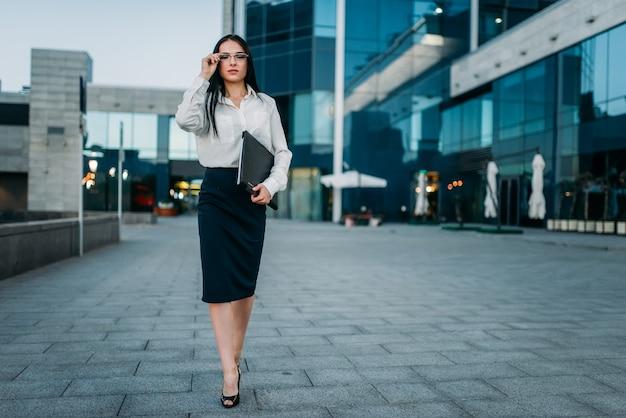 Портрет молодой бизнес-леди в очках и белой блузке с ноутбуком в руке, небоскреб. современное здание, финансовый центр, городской пейзаж.