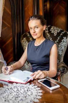 若いビジネスウーマンの肖像画は、ホームオフィスでメモを作成します