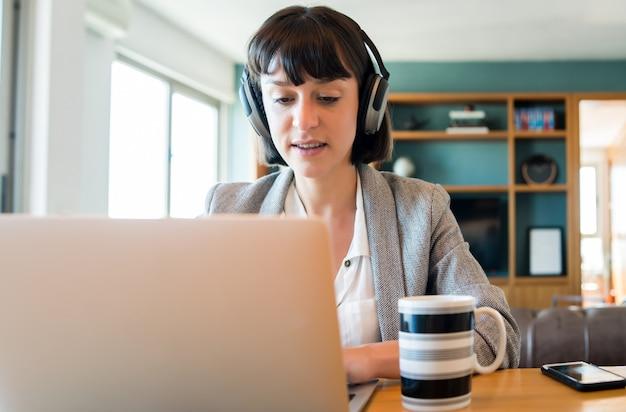Портрет молодой деловой женщины на видеозвонке с ноутбуком и наушниками