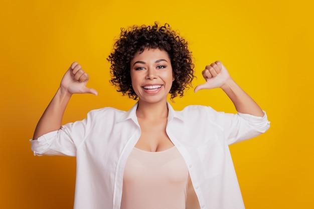 엄지손가락을 가리키는 젊은 비즈니스 여성의 초상화 자신의 조언이 노란색 벽을 선택합니다.