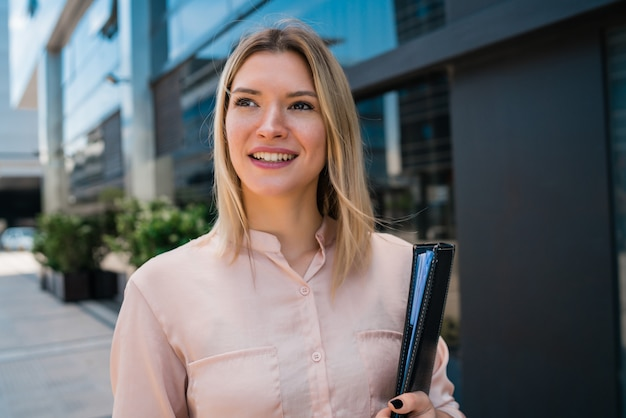 事務所ビルの外に立っている若いビジネス女性の肖像画。ビジネスと成功のコンセプト。