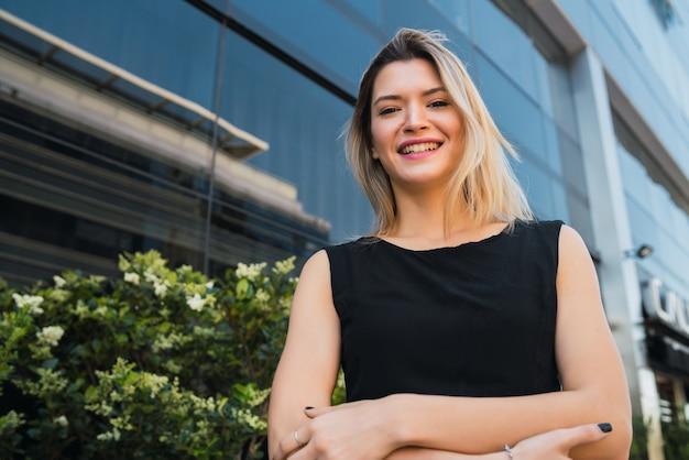 オフィスビルの外に立っている若いビジネス女性の肖像画。ビジネスと成功の概念。