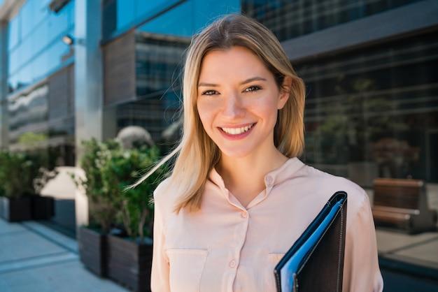 オフィスビルの外に立っている若いビジネス女性の肖像画