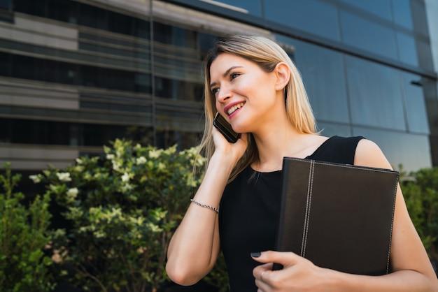 通りで屋外に立っている間電話で話している若いビジネス女性の肖像画。ビジネスコンセプトです。