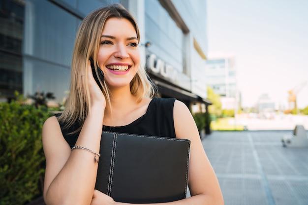事務所ビルの外に立っている間電話で話している若いビジネス女性の肖像画。ビジネスと成功のコンセプト。