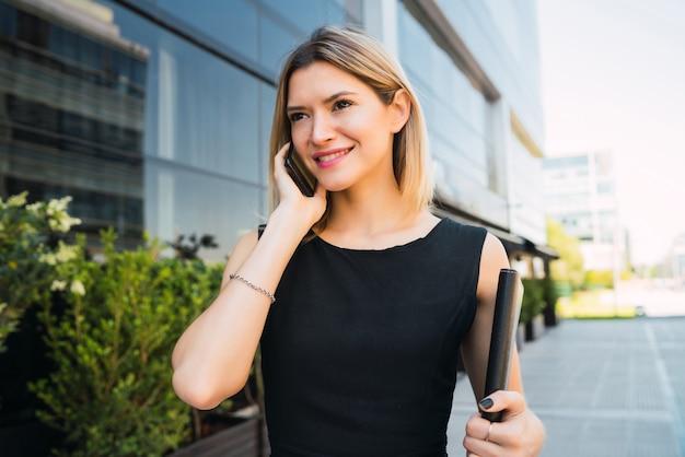 オフィスビルの外に立って電話で話している若いビジネス女性の肖像画。ビジネスと成功のコンセプト。
