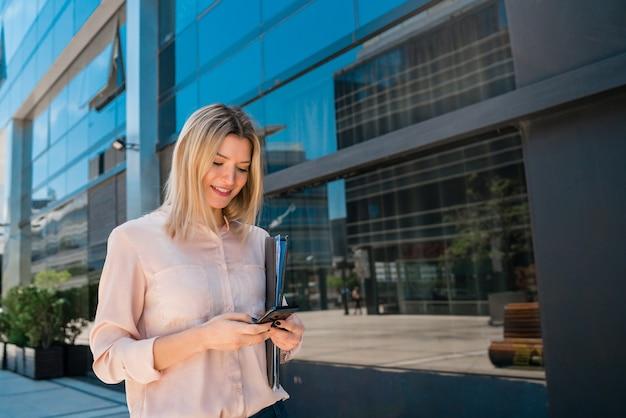 オフィスビルの外に立っているときに彼女の携帯電話を使用して若いビジネス女性の肖像画。ビジネスと成功のコンセプト。