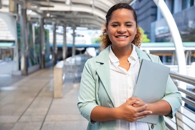 ラップトップで街の通りで働く若いビジネス女性の方法の肖像画。