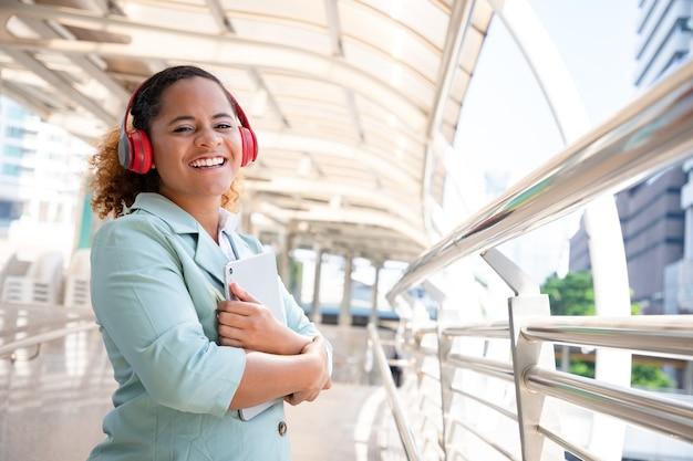 タブレットとヘッドフォンで街の通りで働く若いビジネス女性の方法の肖像画。