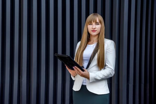 Портрет молодой деловой женщины с планшетом над серой стеной