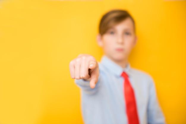 黄色の背景に青年実業家の男の子の肖像画。セレクティブフォーカス