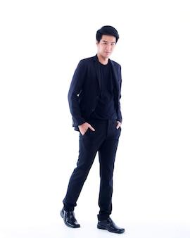 Портрет молодого бизнесмена в черном костюме на белой стене