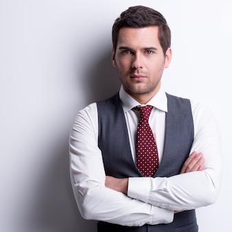 Портрет молодого бизнесмена в сером костюме со скрещенными руками позирует над стеной с контрастными тенями.