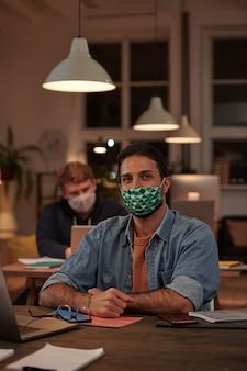 Портрет молодого бизнесмена в защитной маске, глядя вперед, работая за столом в офисе вечером