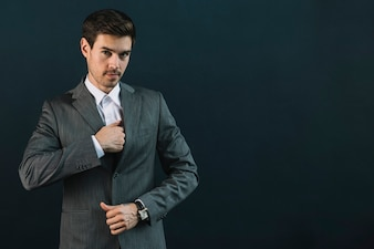 Portrait of young businessman in suit standing against black background