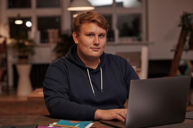 Портрет молодого бизнесмена, глядя на фронт, сидя за столом, работая онлайн на ноутбуке в офисе