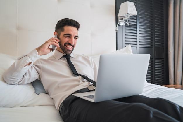 ベッドに横になって、ホテルの部屋で彼のラップトップで作業しながら電話で話している青年実業家の肖像画。出張の概念。