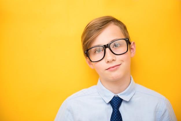 シャツと眼鏡の少年の青年実業家の肖像画。黄色の背景で成功したティーンエイジャー