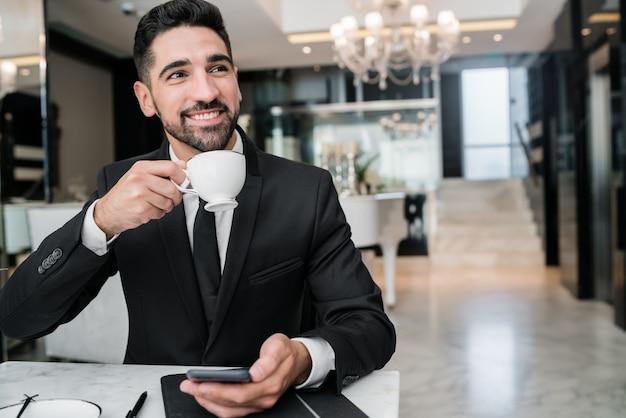 직장에서 휴식과 호텔 로비에서 커피를 마시는 젊은 사업가의 초상화. 출장 및 여행 개념.