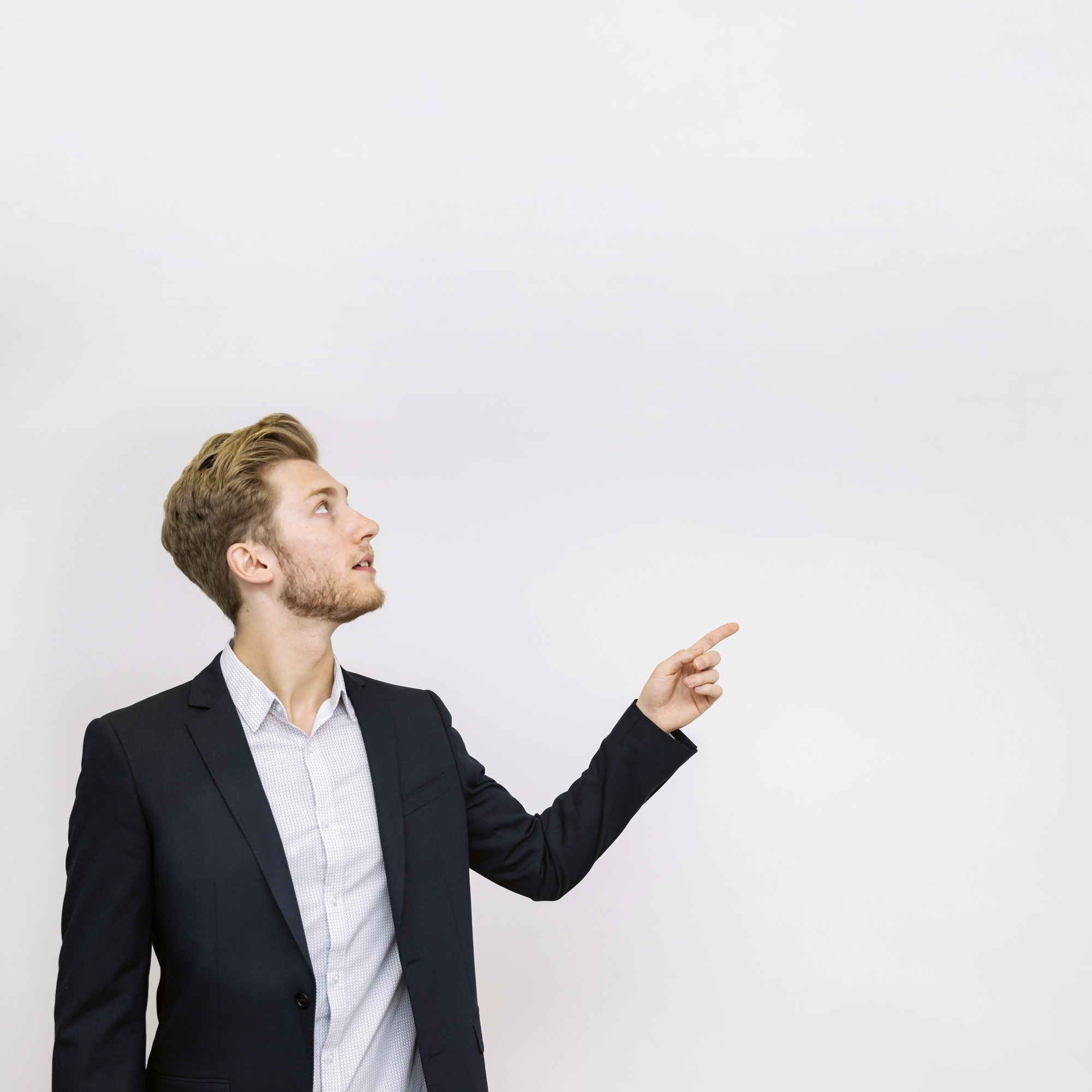 Portrait of young businessman pointing at something looking up