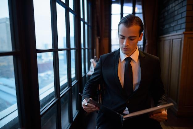 Портрет молодого бизнесмена, читая меню в ресторане
