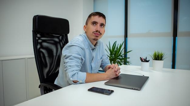 사무실에서 컴퓨터의 그의 책상 앞에 앉아 젊은 사업가의 초상화. 일부 프로젝트에서 노트북으로 작업하는 자신감있는 기업가