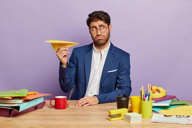 Портрет молодого бизнесмена, сидящего за офисным столом