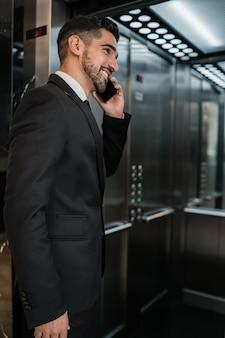 호텔 엘리베이터에서 전화 통화하는 젊은 사업가의 초상화. 비즈니스 여행 개념.