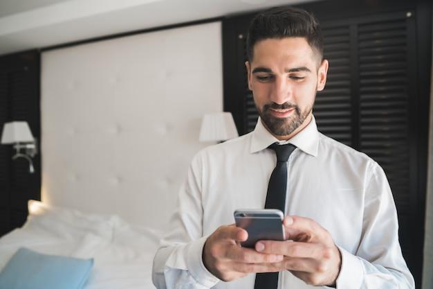 ホテルの部屋で彼の携帯電話を使用して青年実業家の肖像画。出張の概念。
