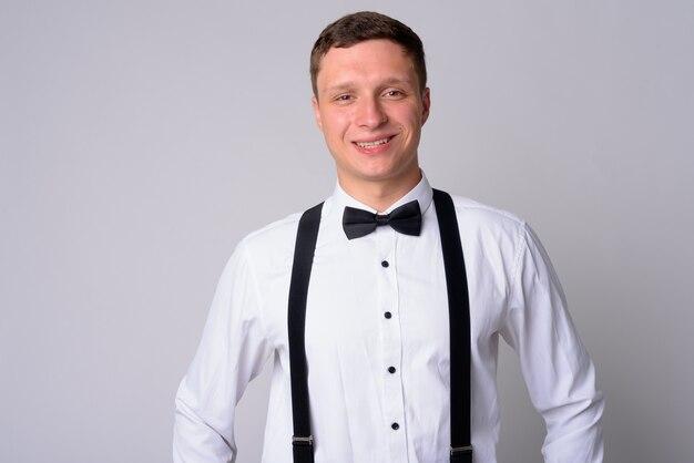 Портрет молодого бизнесмена в подтяжках на белой стене