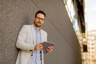 Portrait of young businessman with digital tablet standing outdoor