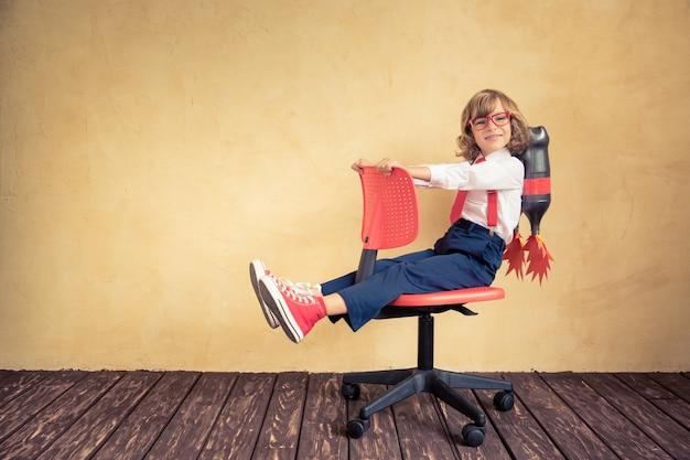 Портрет молодого бизнесмена с реактивным ранцем верхом на офисном кресле