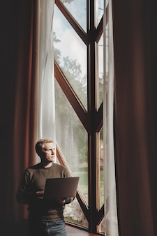 Портрет молодого бизнесмена с ноутбуком в окне гостиной в загородном доме. трудоголик в домашней повседневной одежде, работает в отпуске. творческое вдохновение и запуск бизнеса. копировать пространство