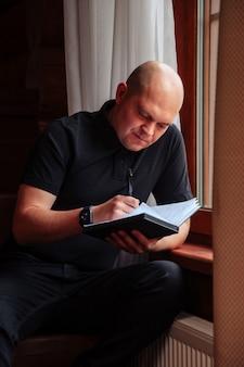 カントリーハウスのリビングルームの窓にノートと電話を持つ青年実業家の肖像画。休暇で働いている家庭のカジュアルな服を着たworkaholic男。クリエイティブなインスピレーションとスタートアップビジネス