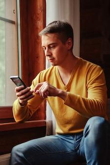 Портрет молодого бизнесмена с ноутбуком и телефоном в окне гостиной в загородном доме. трудоголик в домашней повседневной одежде, работает в отпуске. творческое вдохновение и запуск бизнеса