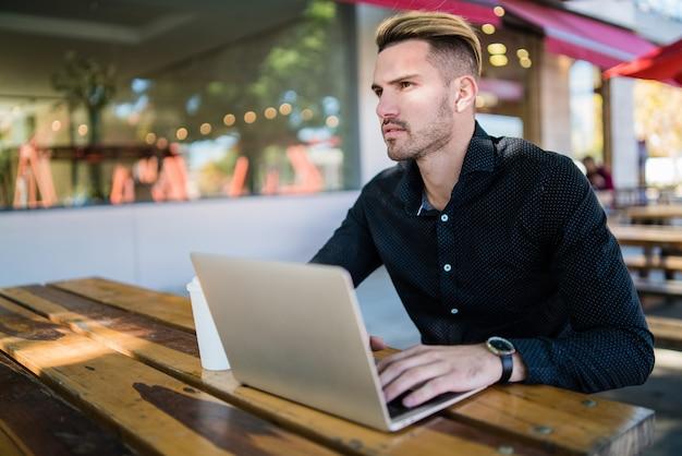 Портрет молодого бизнесмена, работающего на своем ноутбуке, сидя в кафе. технологии и бизнес-концепция.